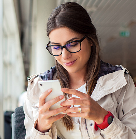 A woman in glasses holding a mobile phone